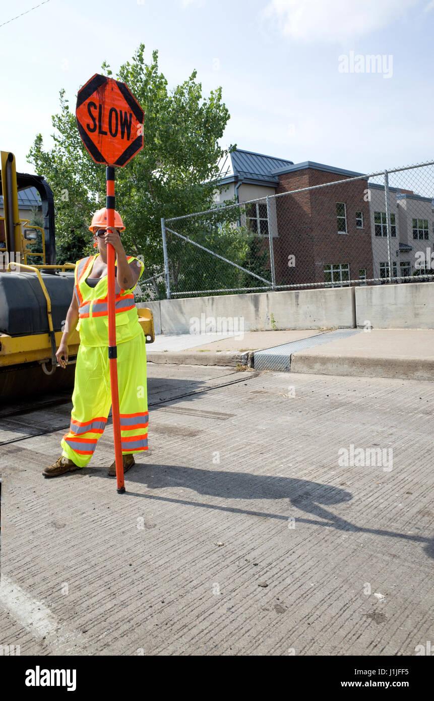 Women on road crew holding a slow sign. Minneapolis Minnesota MN USA - Stock Image