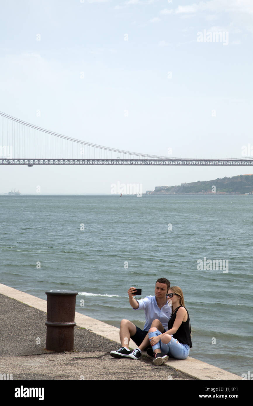 A couple taking a selfie in front of the  25 de Abril Bridge in Lisbon, Portugal. Stock Photo