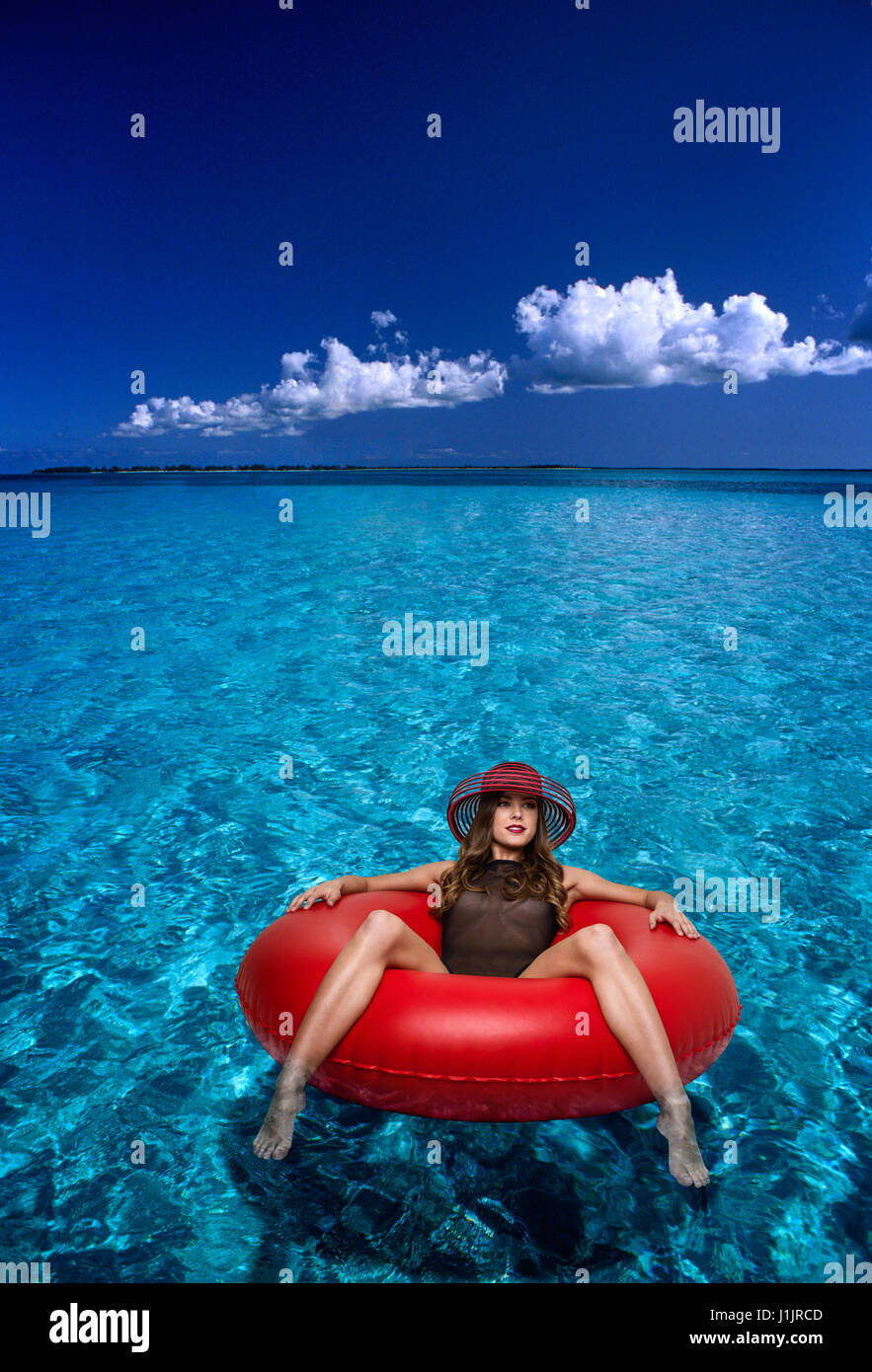 Young woman floating in an inner tube - Stock Image