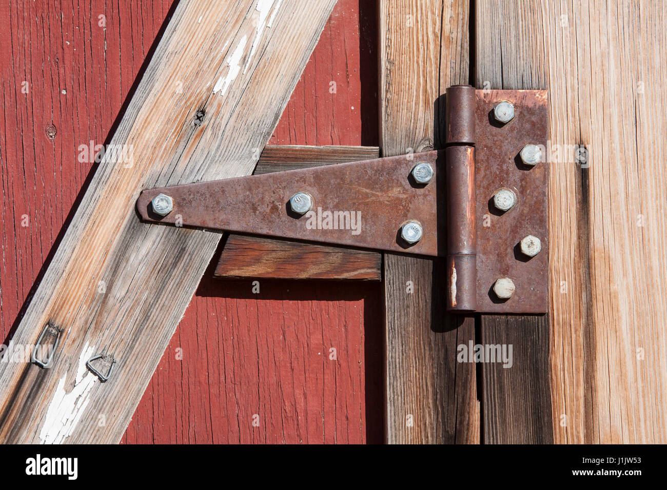 Closeup detail of rusting hinge on a weathered barn door. Hodgepodge of fasteners hold hinge and door together. - Stock Image