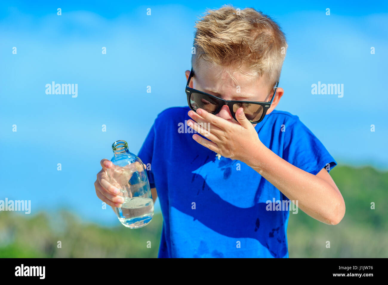 Portrait of a thirsty handsome boy in sunglasses drinking water on the desert tropical beach - Stock Image
