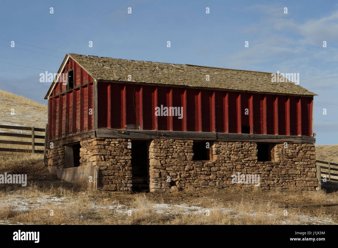 Old red granary. Fading paint, missing shingles, general disrepair give character to exposed frame and stone building. - Stock Image