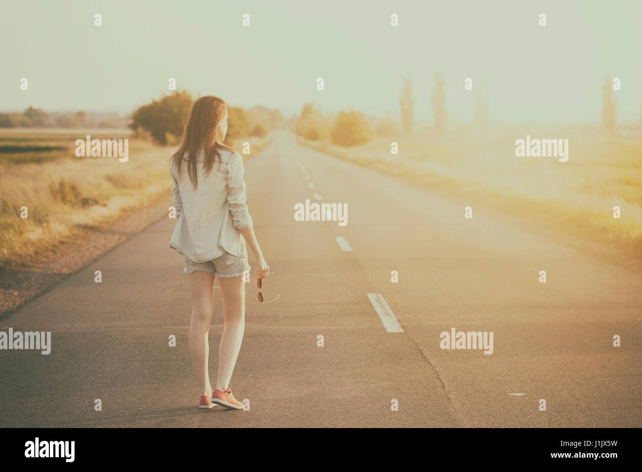 Hitchhiker woman on the road in summer sunset - Stock Image