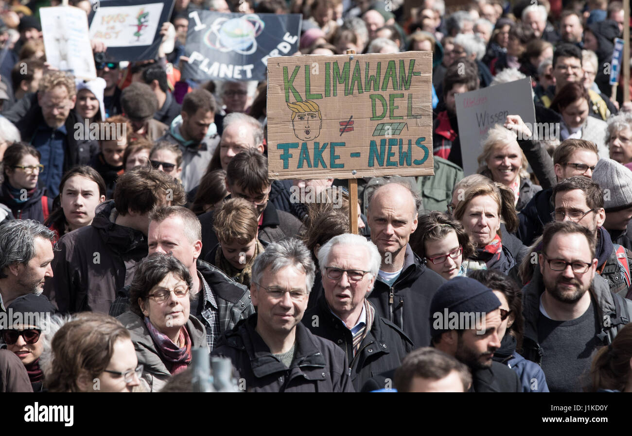 """Berlin, Germany. 22nd Apr, 2017. Protestors hold up a sign reading """"Climate Change is not Fake News"""" during the Stock Photo"""