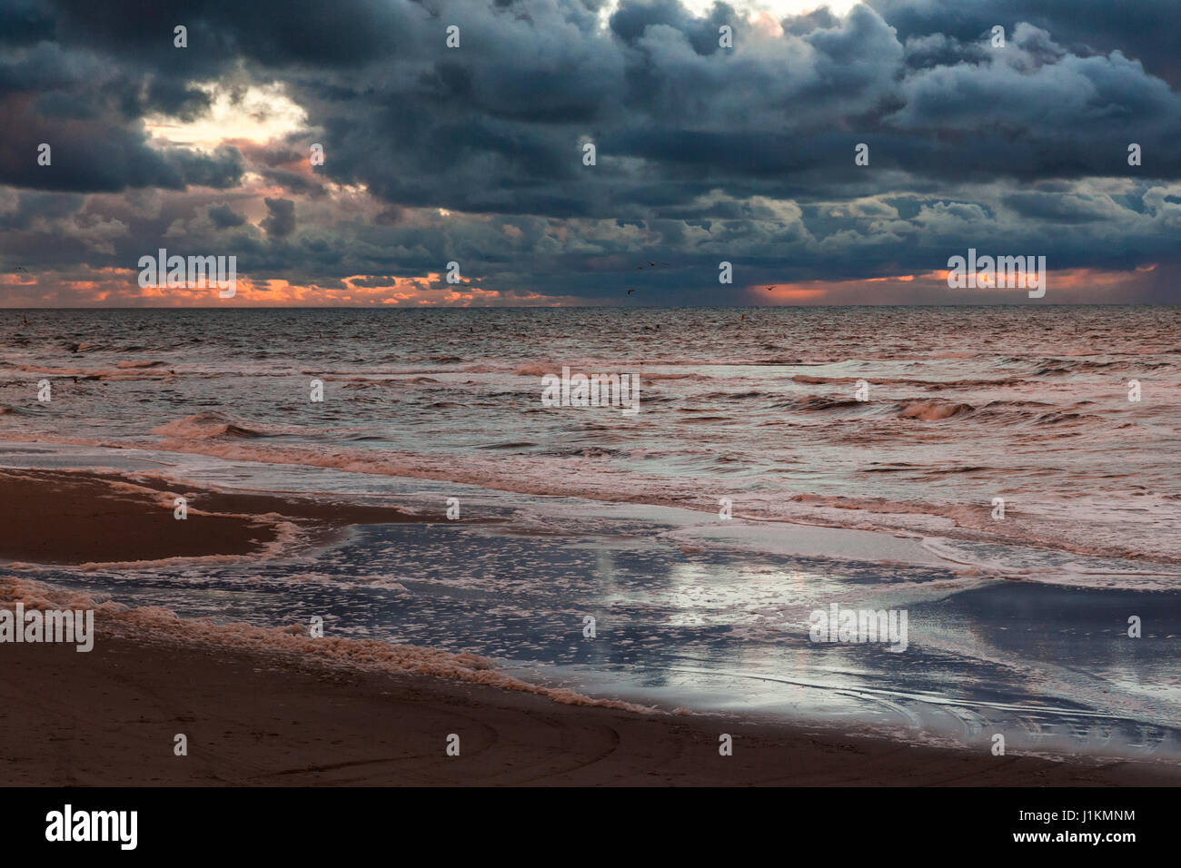 Dark sky and sunset above the sea on the island of Texel - Stock Image
