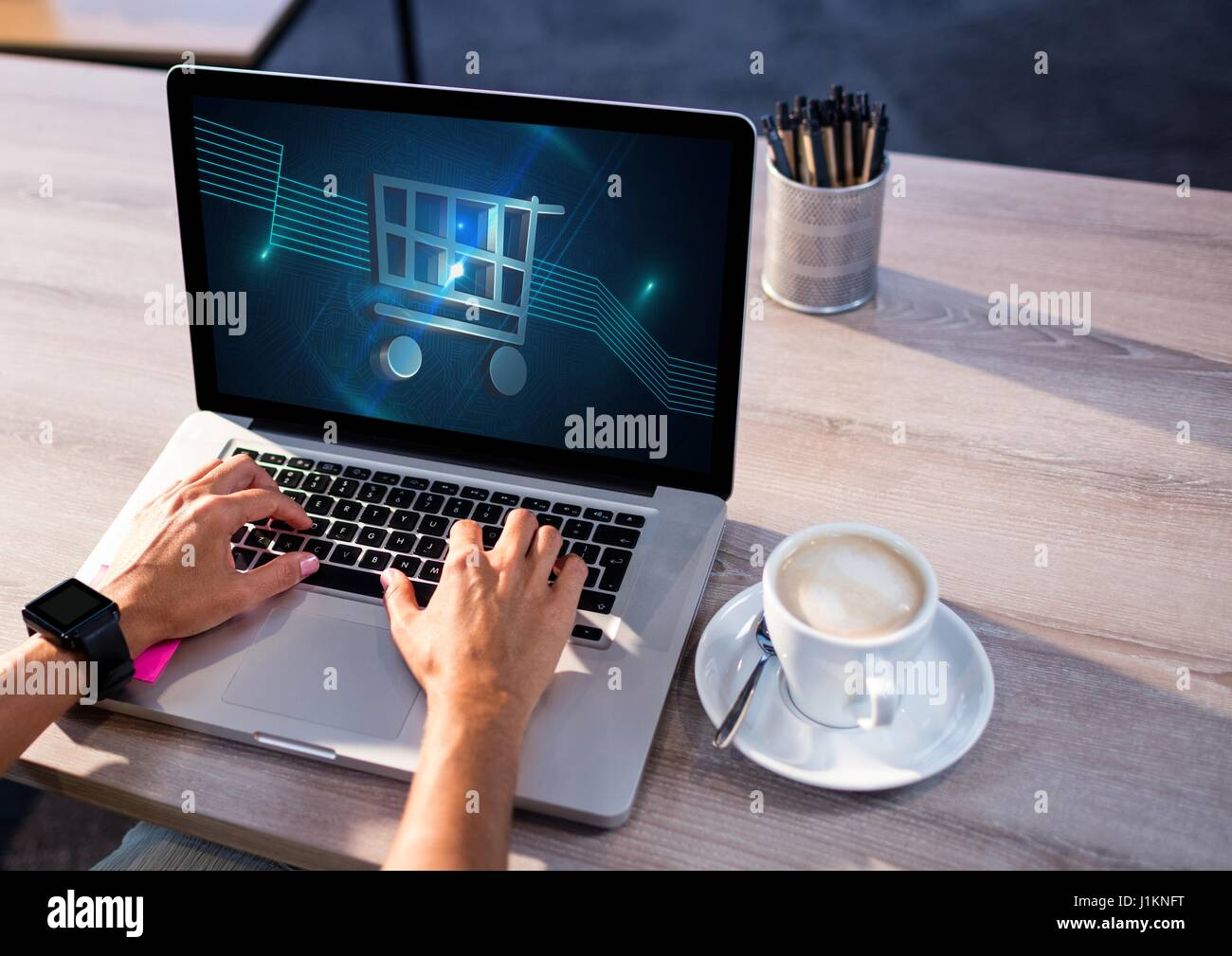 Digital composite of Person using Laptop with Shopping trolley icon - Stock Image