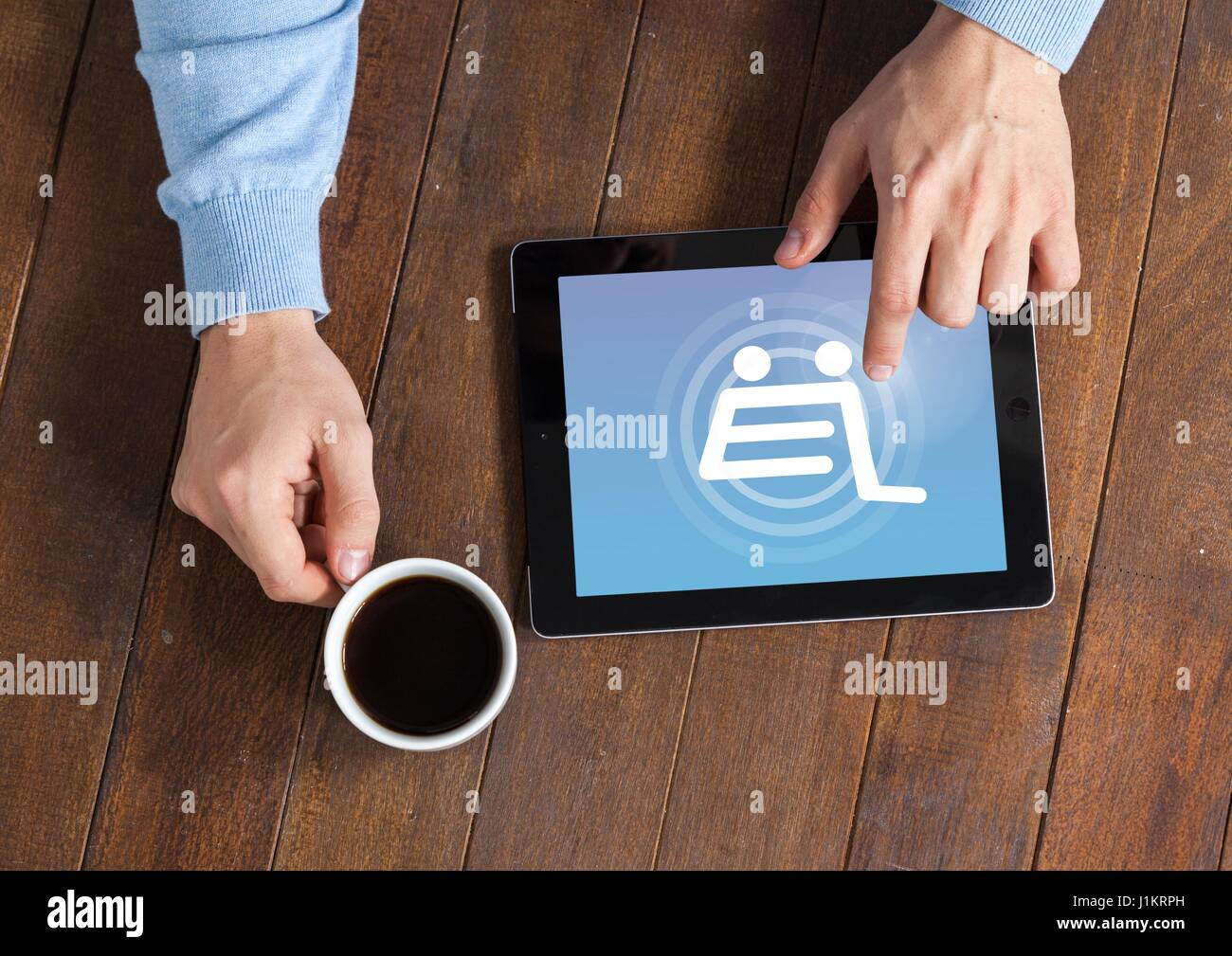 Digital composite of Man using Tablet with Shopping trolley icon and coffee - Stock Image