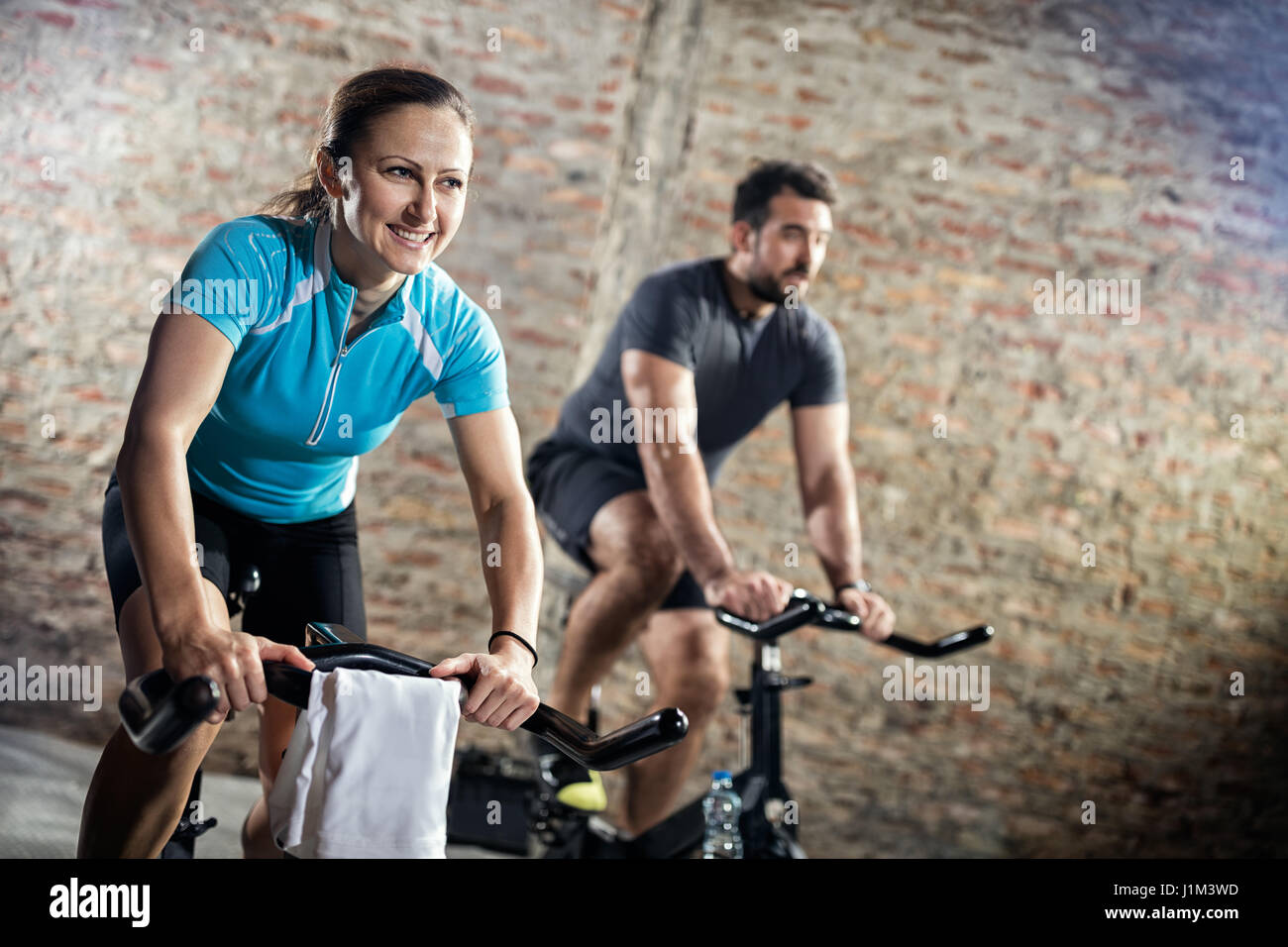 Smiling woman in sports clothing on cycling fitness training - Stock Image