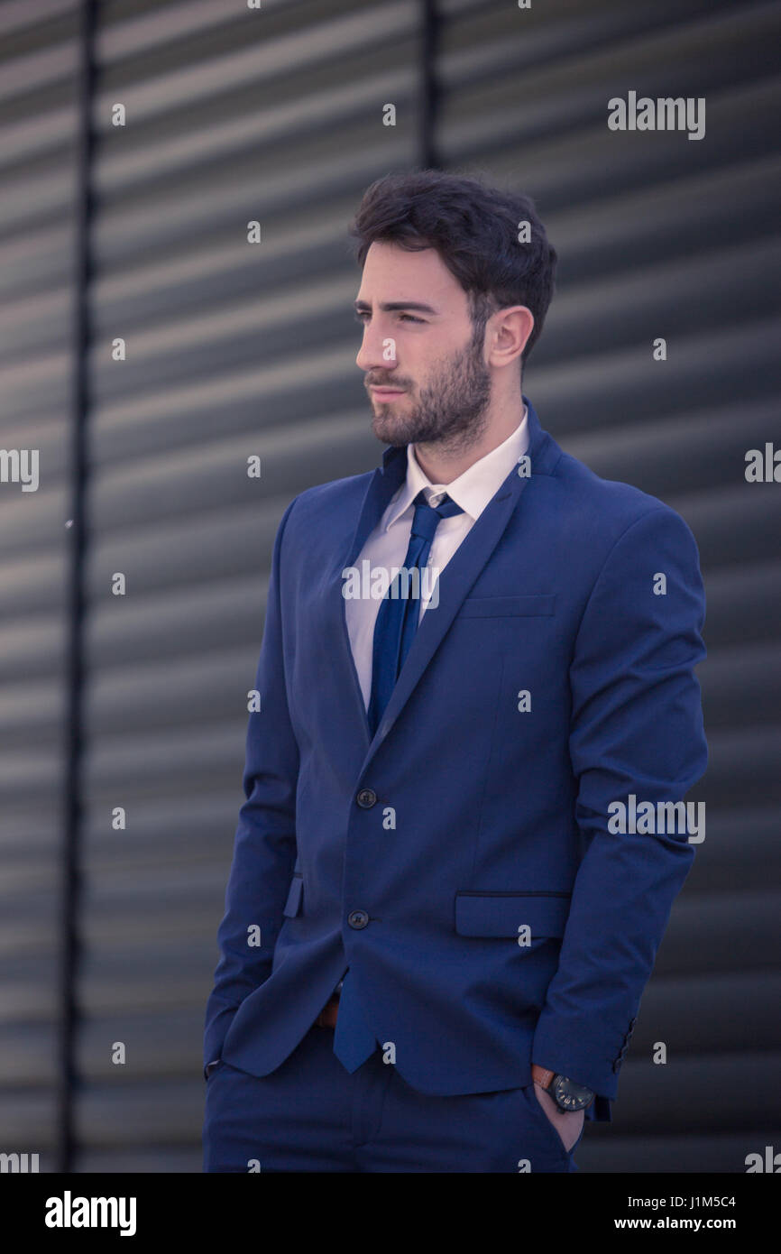 one young man standing, formal wear suit, looking sideways, outdoors - Stock Image