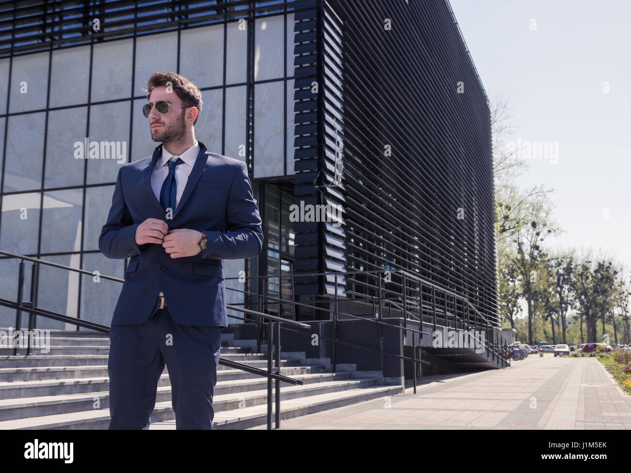 one young man, formal wear, suit tie sunglasses, buttoning suit, street modern building, outdoors day - Stock Image