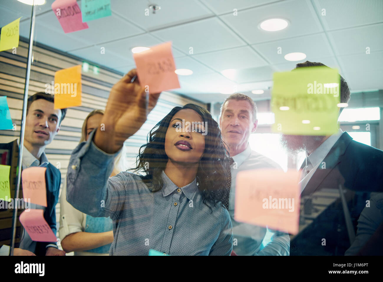 Young black businesswoman explaining business strategy to the staff in the office. Mixed team of entrepreneurs brainstorming - Stock Image