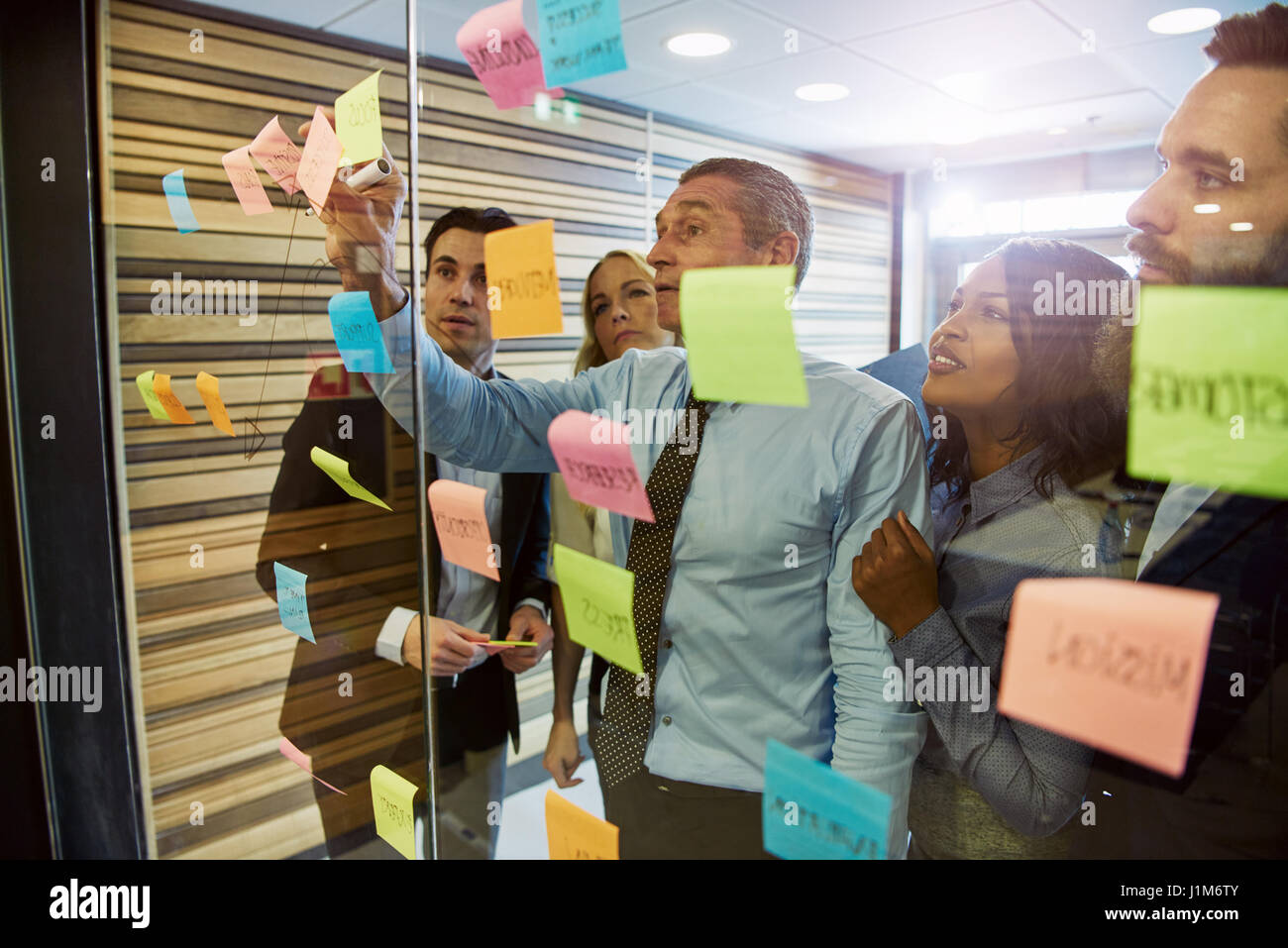 Mixed group of business people having a standing meeting at the office. Using stickers and posters on window to - Stock Image