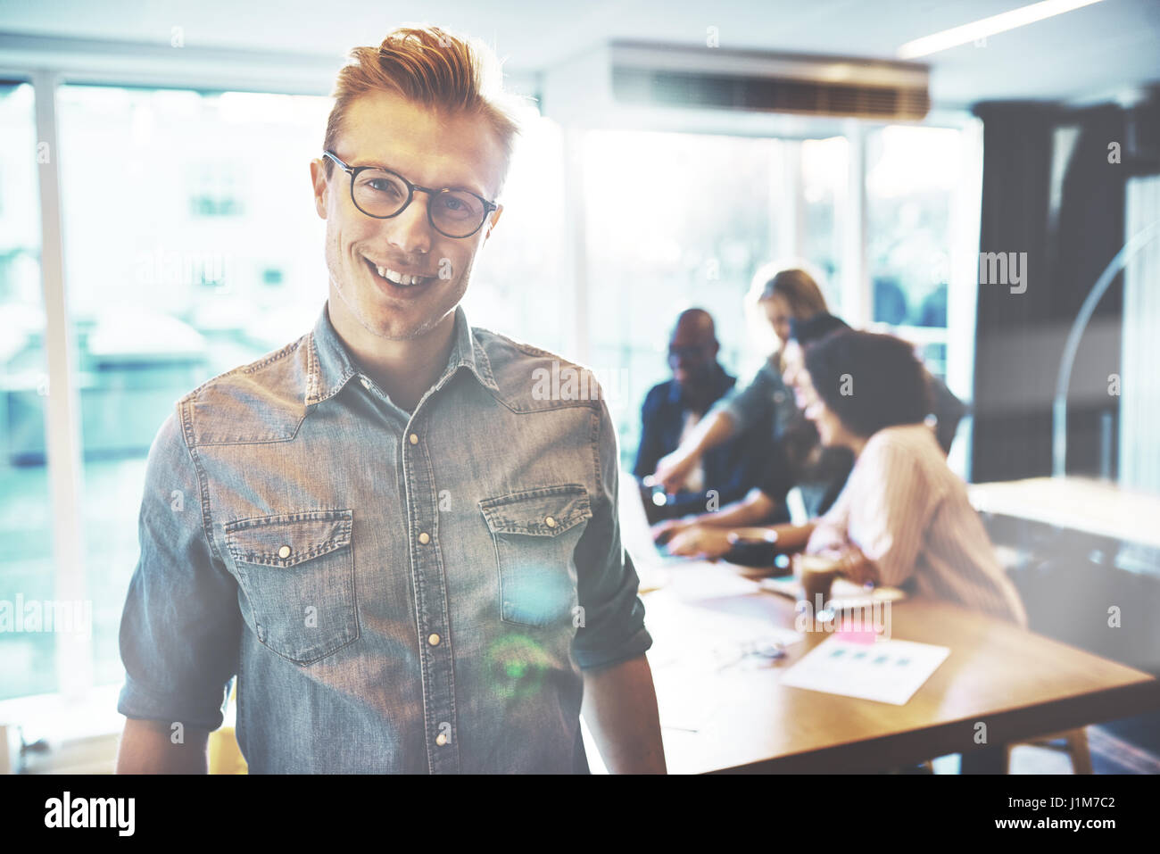 Cheerful handsome man in eyeglasses near partners in obscured background at a small office - Stock Image