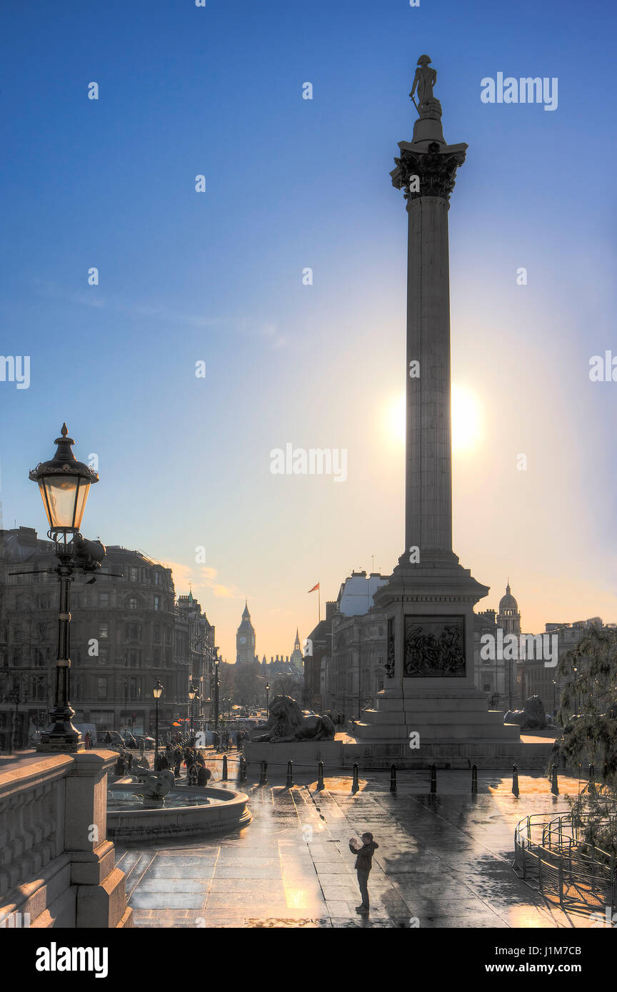 Nelson's Column in Trafalgar Square, London with the sun behind the column and The Mall stretching out behind - Stock Image