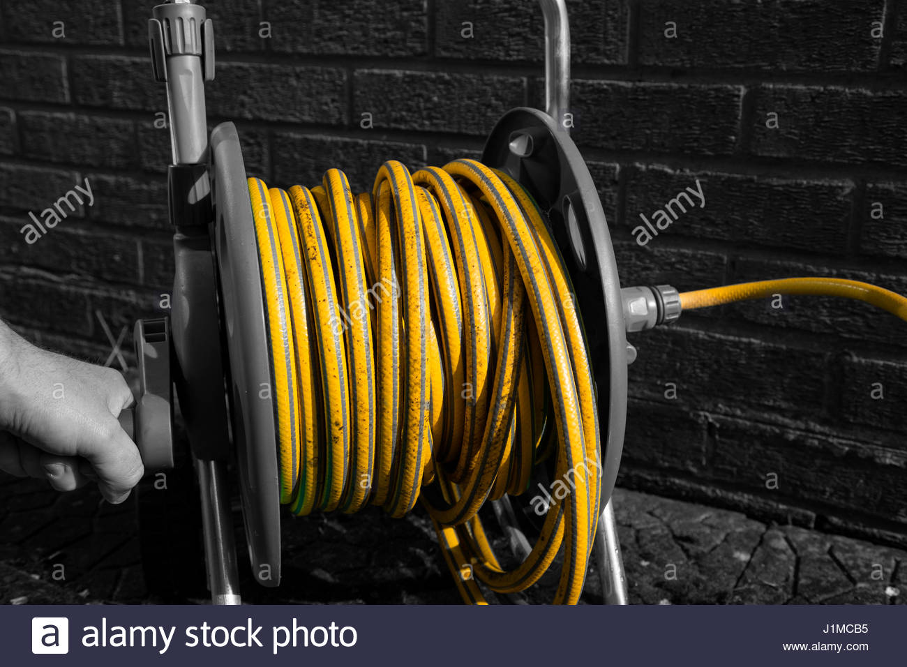 Selective colour image of a man winding a hose pipe reel - Stock Image & Garden Hose Reel Stock Photos u0026 Garden Hose Reel Stock Images - Alamy