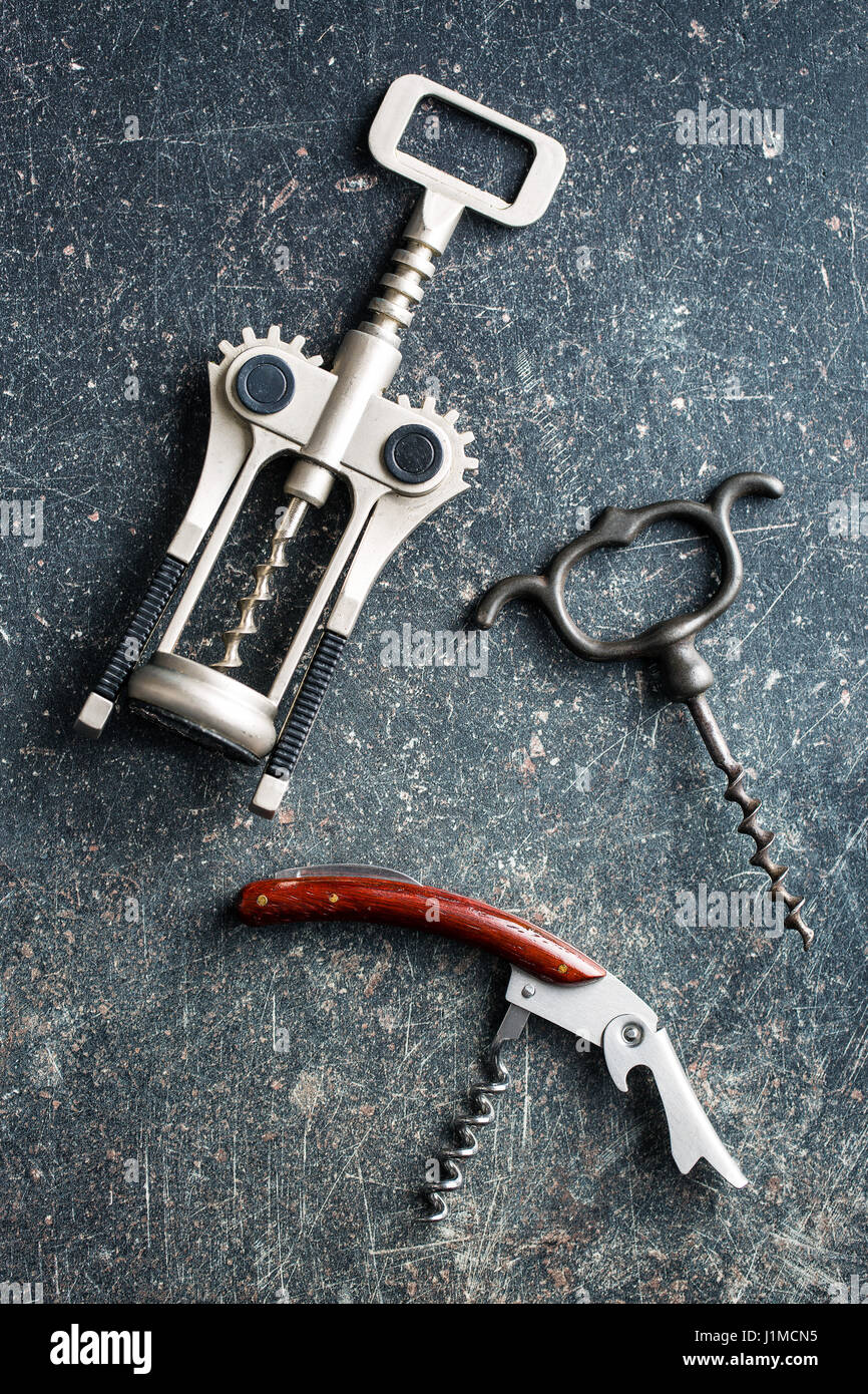 Various types of corkscrews on old kitchen table. - Stock Image