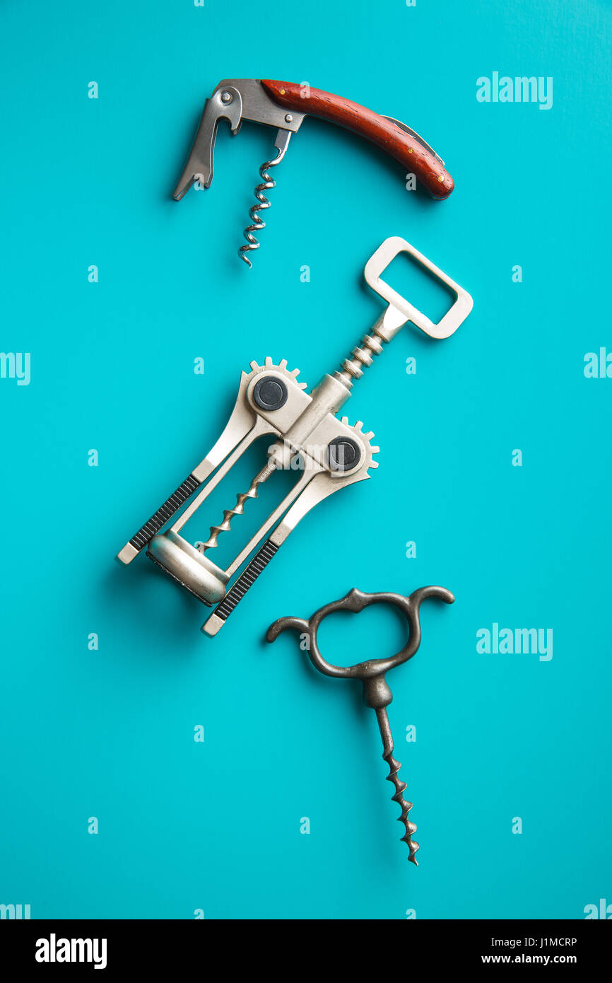 Various types of corkscrews on blue background. - Stock Image