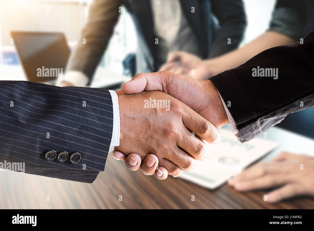 Acquisition concept,Handshake of businessmen on blur businesspeople background, vintage tone and greeting, dealing, - Stock Image