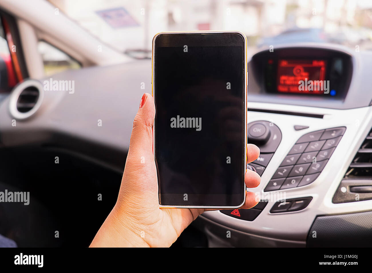 Close up Young female driver using touch screen smartphone and gps navigation in a car, concept using smart phone - Stock Image