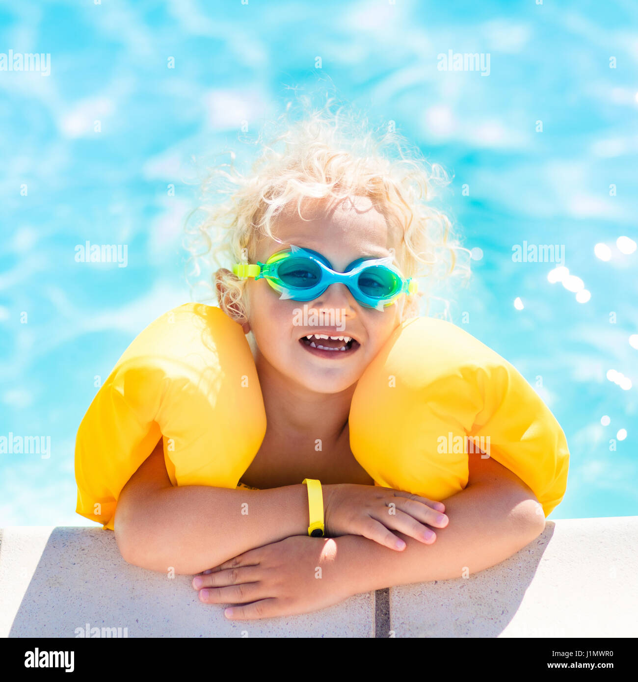81fadc8d21 Happy laughing little baby boy playing in outdoor swimming pool on a hot  summer day. Kids learn to swim. Child with colorful floaties. Swimming aid  fo