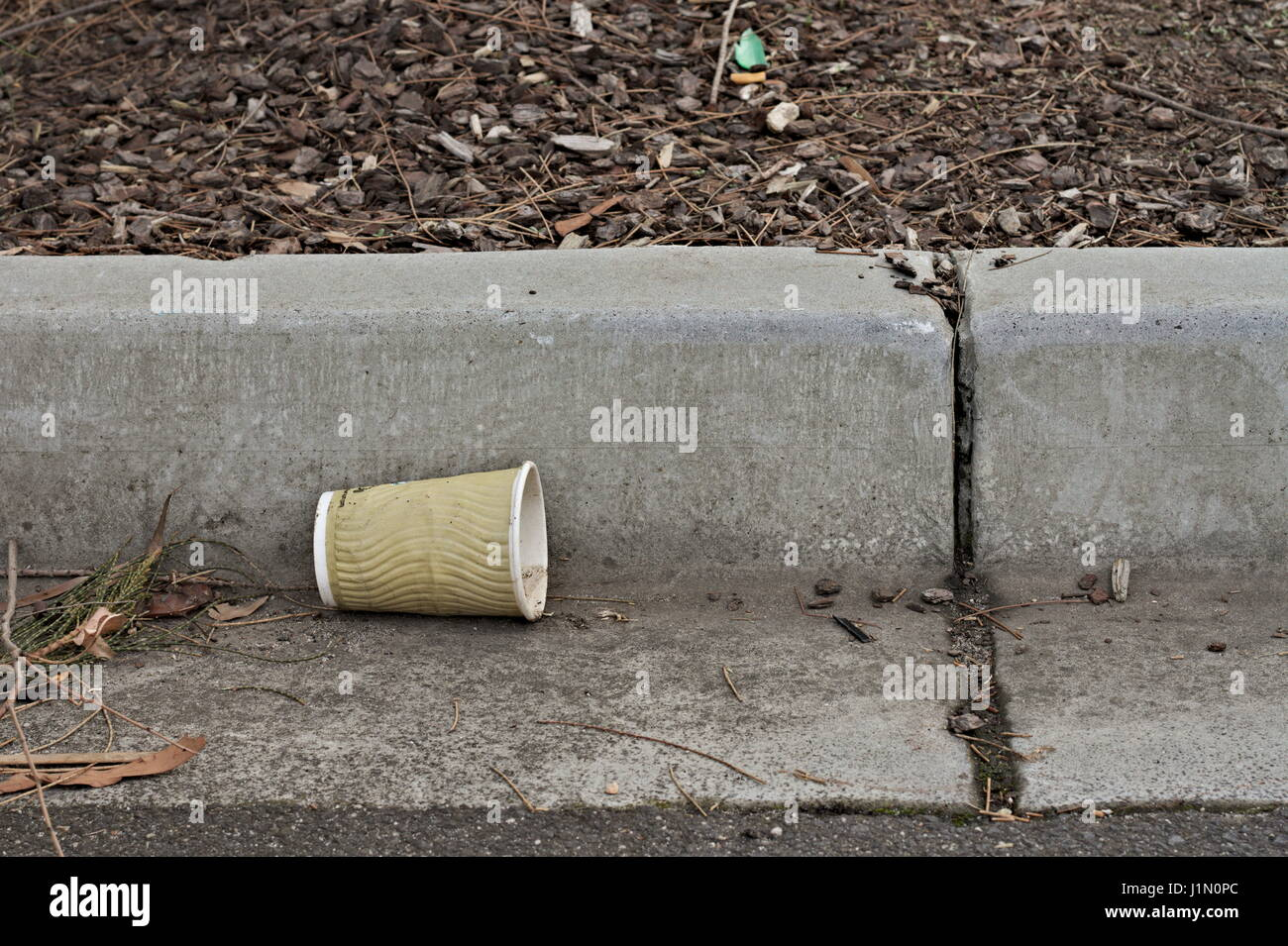 Takeaway coffee cup thrown away in the gutter as trash. - Stock Image