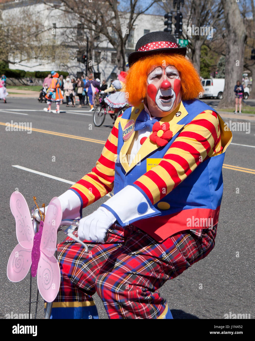 Clown riding  bike during street parade - USA Stock Photo