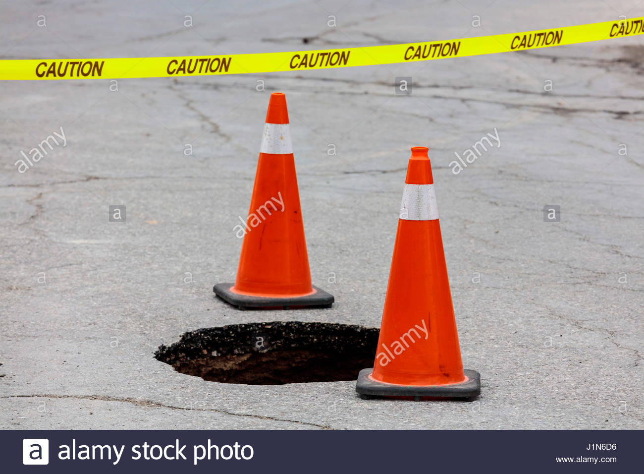 Sinkhole in road caused by water main break marked by traffic cone and caution tape in Toronto Ontario Canada. - Stock Image