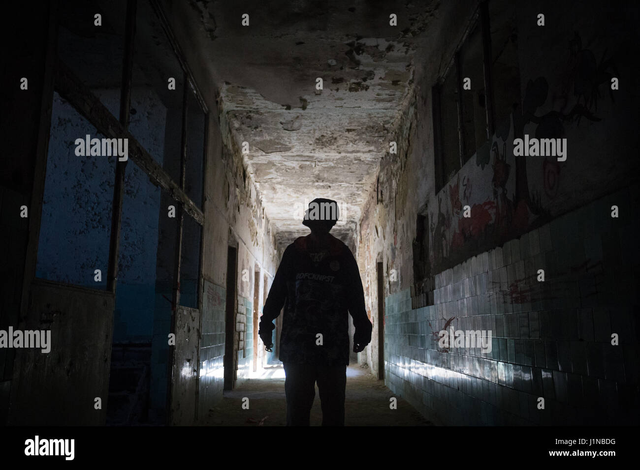 Man in a dark abandoned hospital building - Stock Image