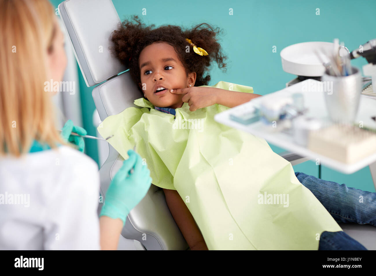 Very cute black kid in dental chair showing aching tooth - Stock Image