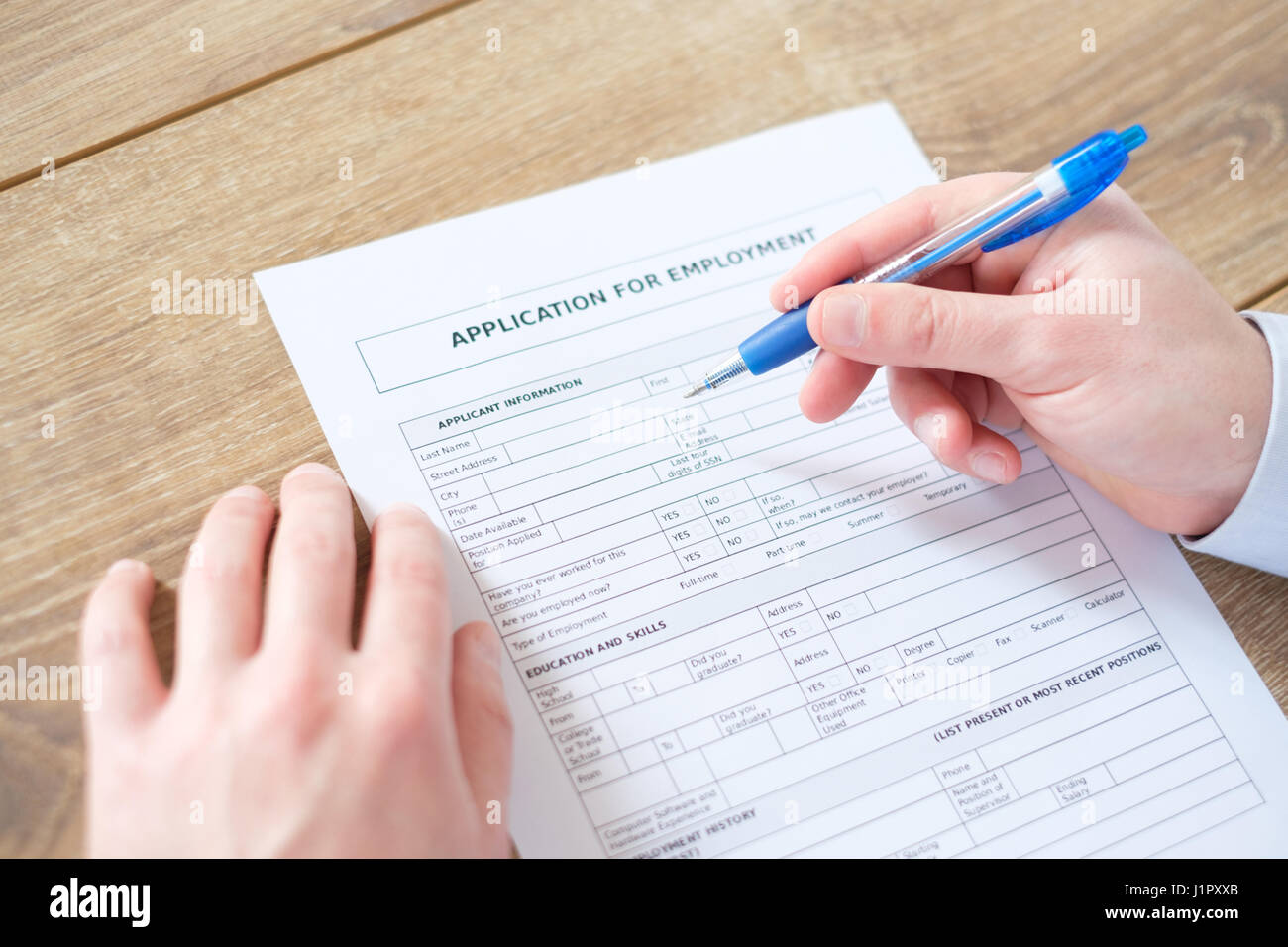 Hand filling the job resume application for employment - Stock Image