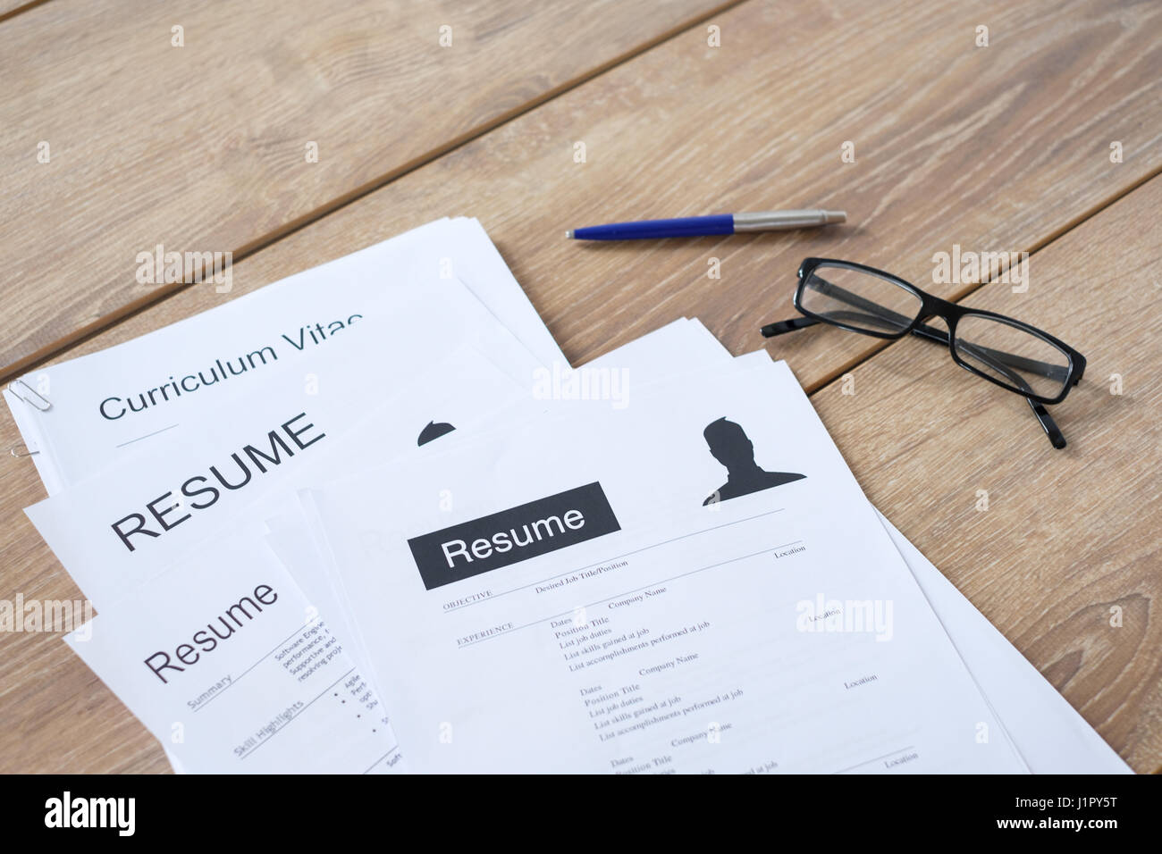 Resume applications on wooden desk ready to be reviewed - Stock Image
