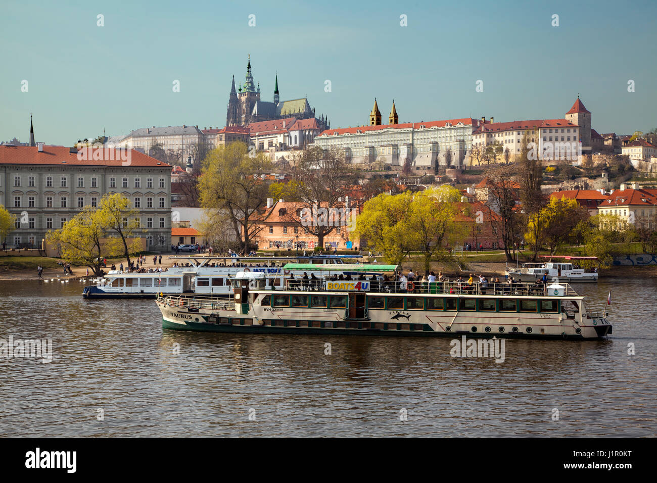 View across the river Vltava towards Prague Castle showing a boat doing sightseeing trips in springtime - Stock Image