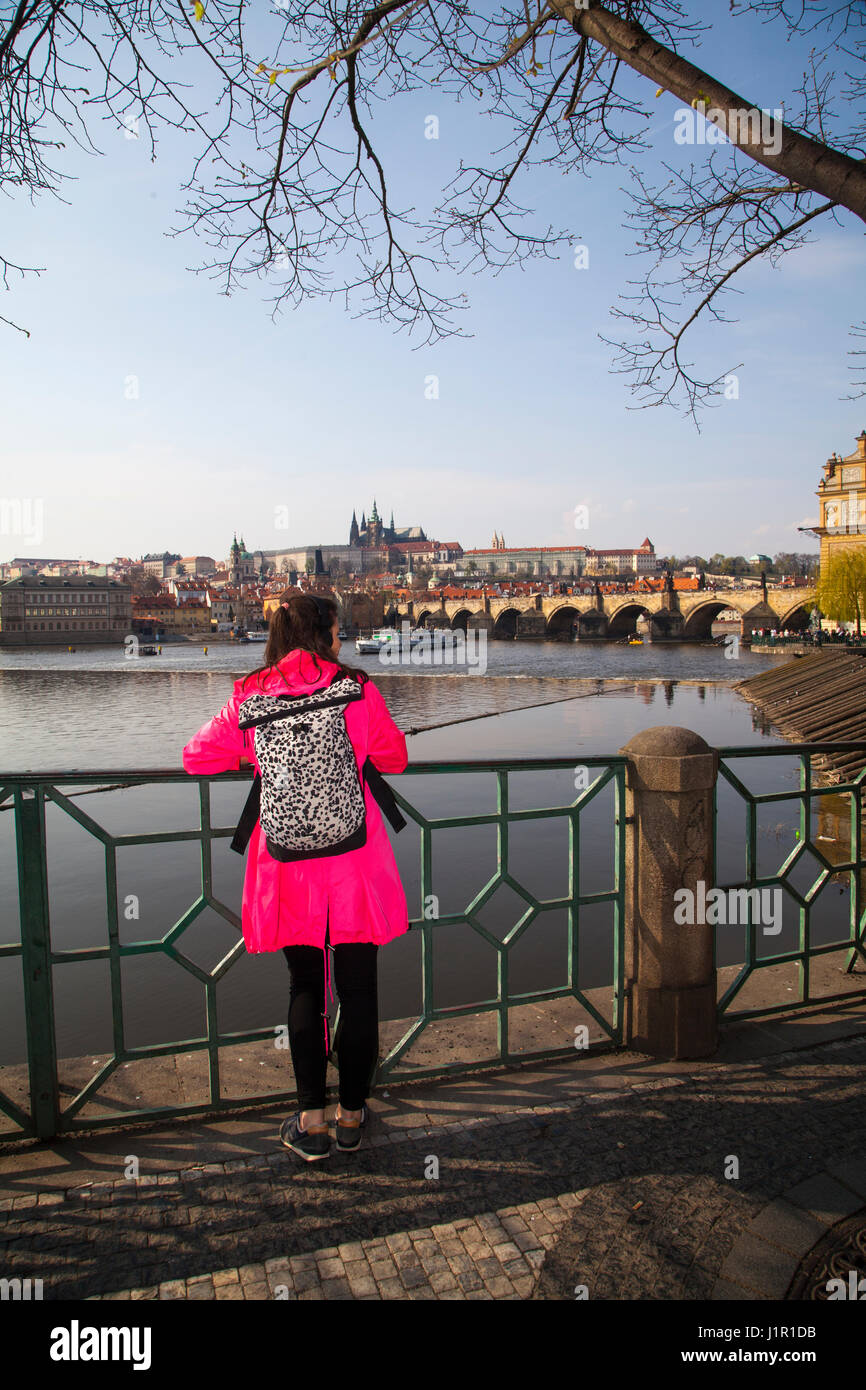 Girl in a pink coat and wearing a back pack taking in the view over the river Vltava looking towards the Charles - Stock Image