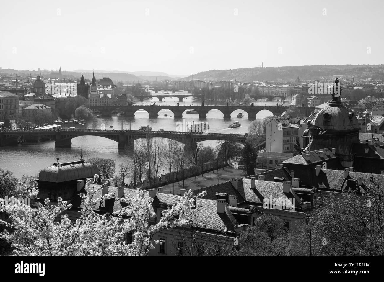 View over the roof tops of Prague showing some of its many bridges over the river Vltava taken in black and white - Stock Image
