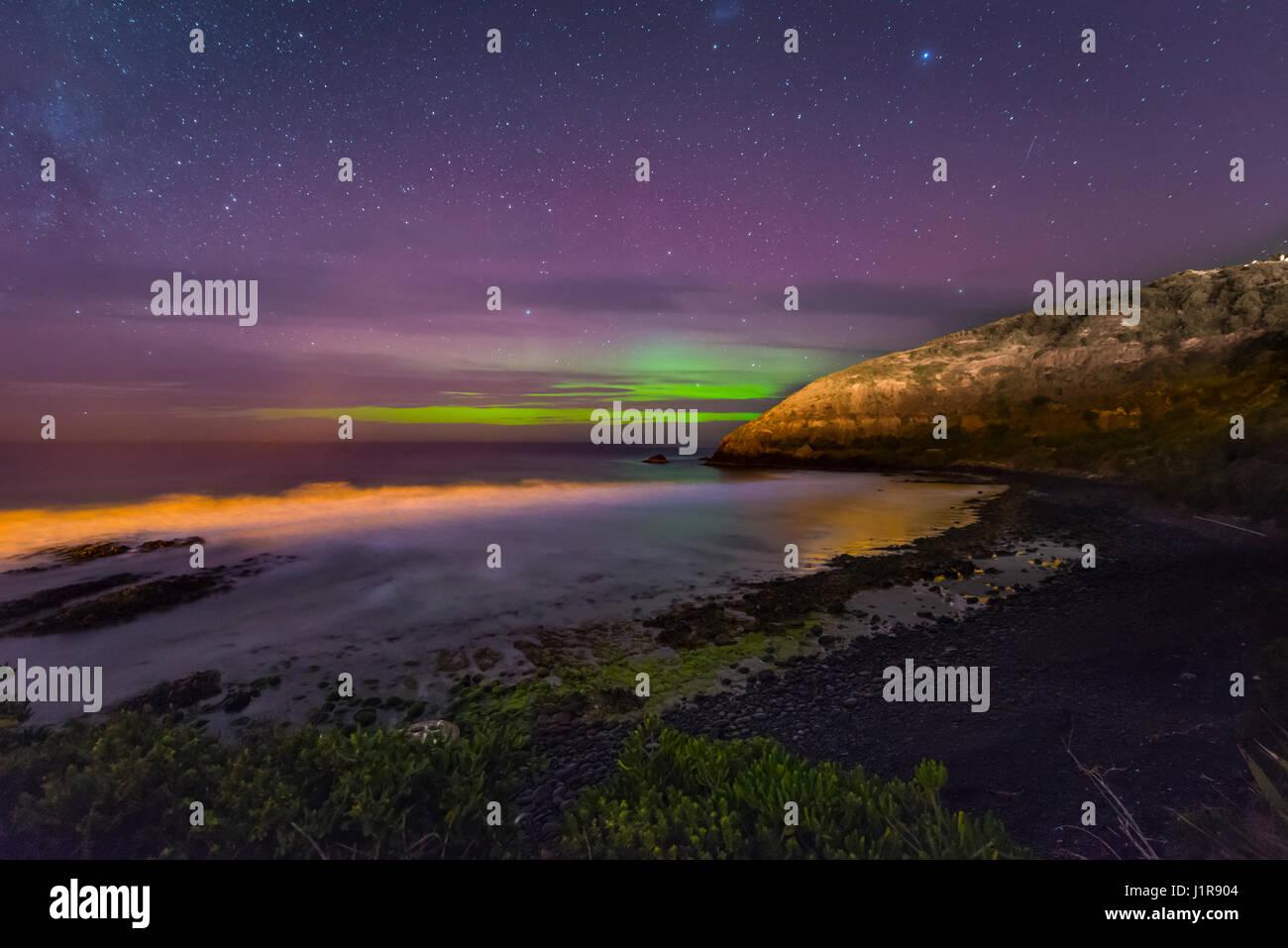 Southern lights, aurora australis over the sea, sand dunes, Second Beach, Dunedin, Otago, Southland, New Zealand - Stock Image
