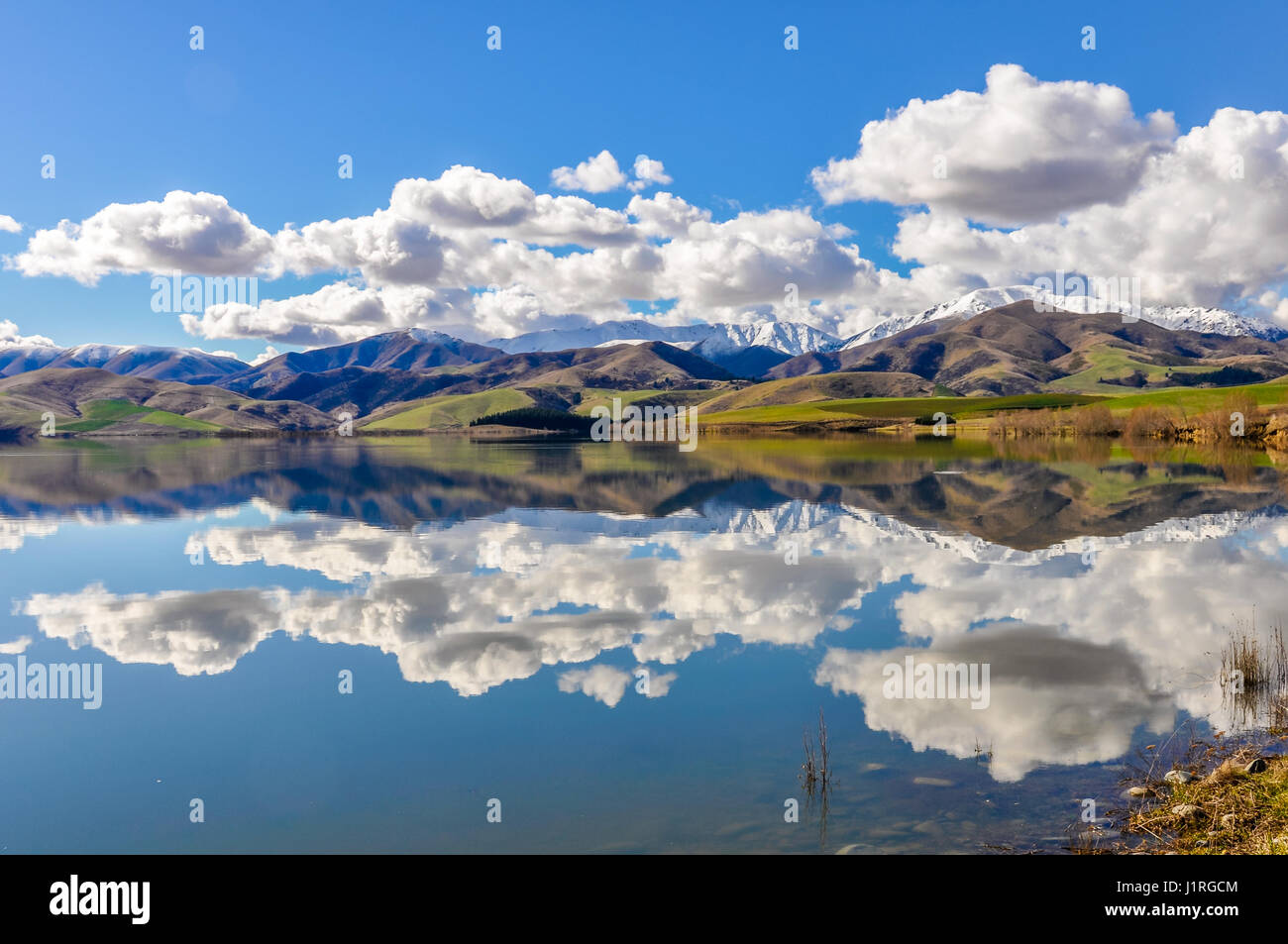 Reflection of the snowy mountains in a lake near Fairlie in the Southern Island, New Zealand - Stock Image