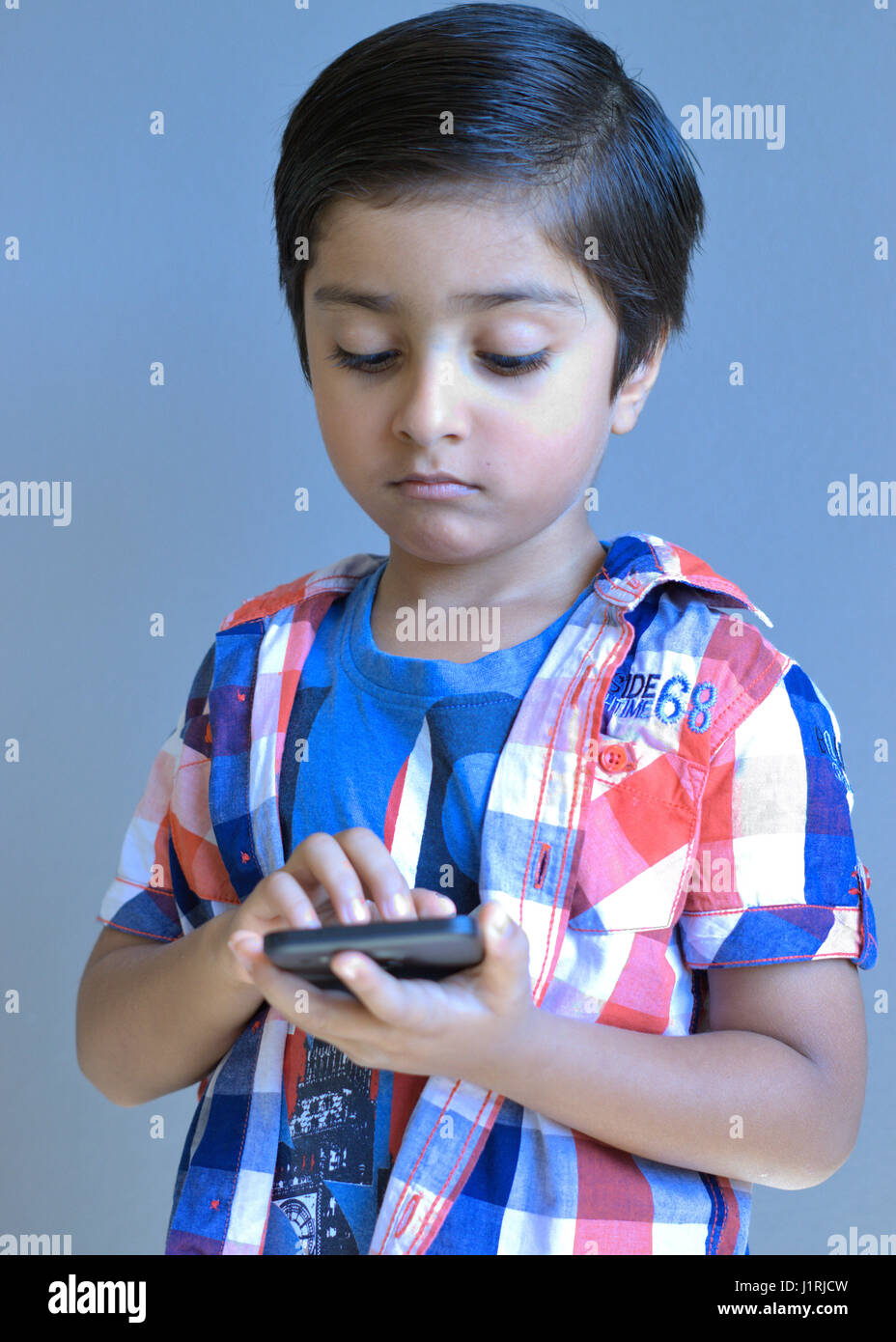 Kid with mobile phone. Kid with cell phone. Kid using mobile. Child tapping on mobile phone. - Stock Image