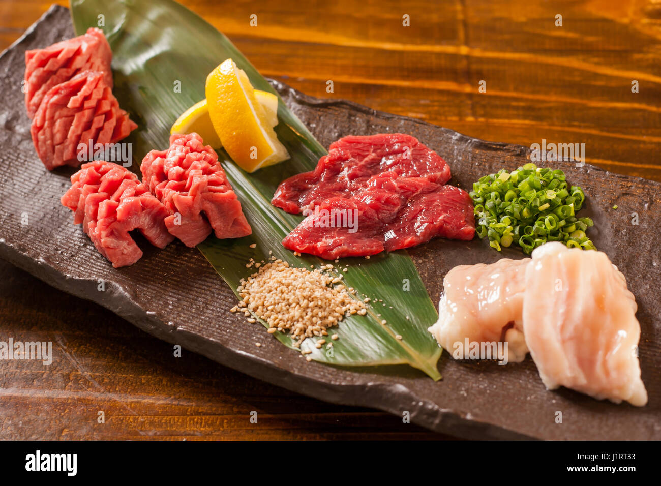 Fresh raw red beef with lemon on stone cutting board Stock Photo