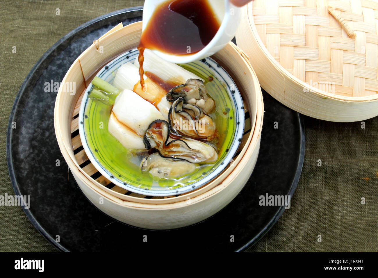 Oyster soup with produce and radish in bamboo tray - Stock Image