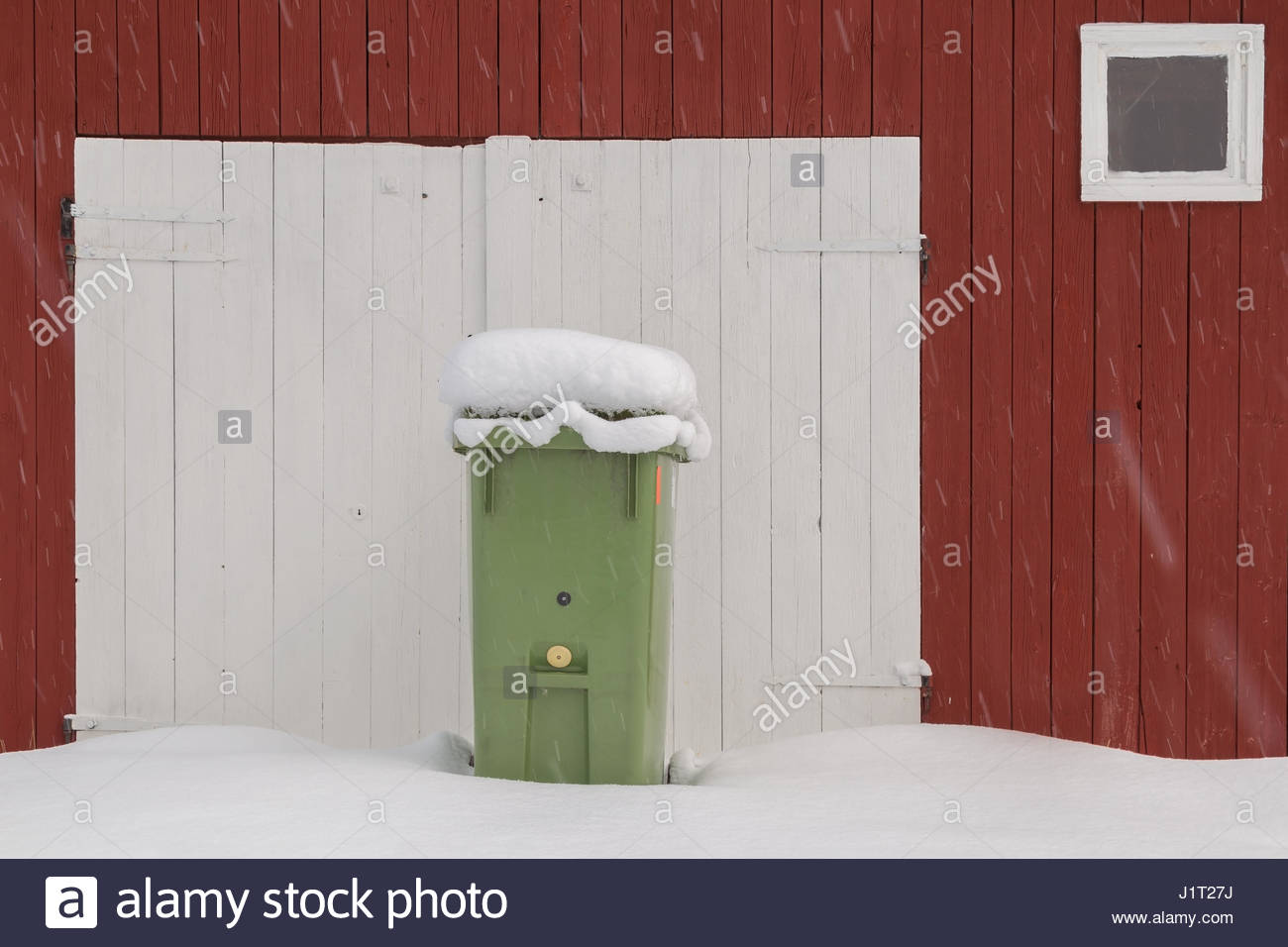 red swedish barn in snow with a wheeled trash can while snowing - Stock Image