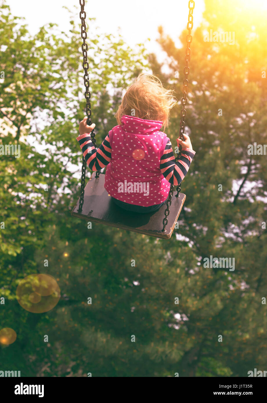 Toddler girl on the swing - Stock Image