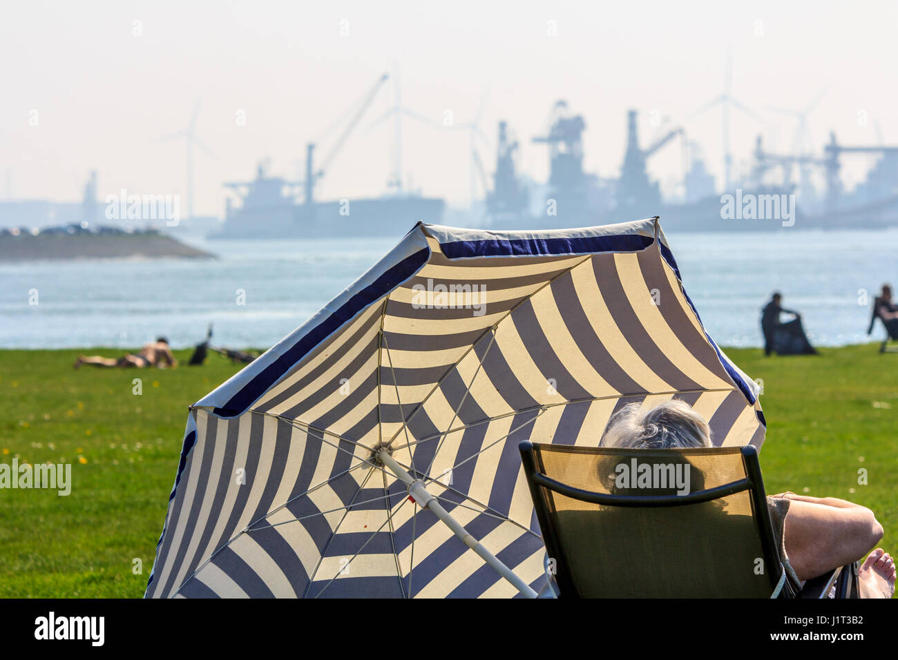 Hoek van Holland, the Netherlands - April 09, 2017: people relaxing in the sun near busy prt Rotterdam - Stock Image