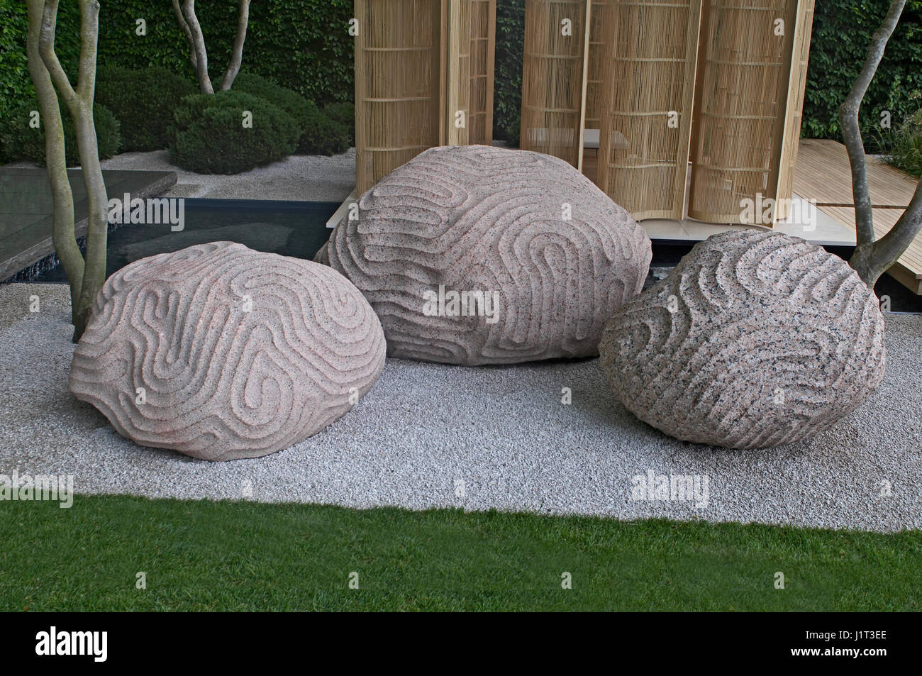 Sculpture showing the intervention of humans into nature in a garden setting - Stock Image