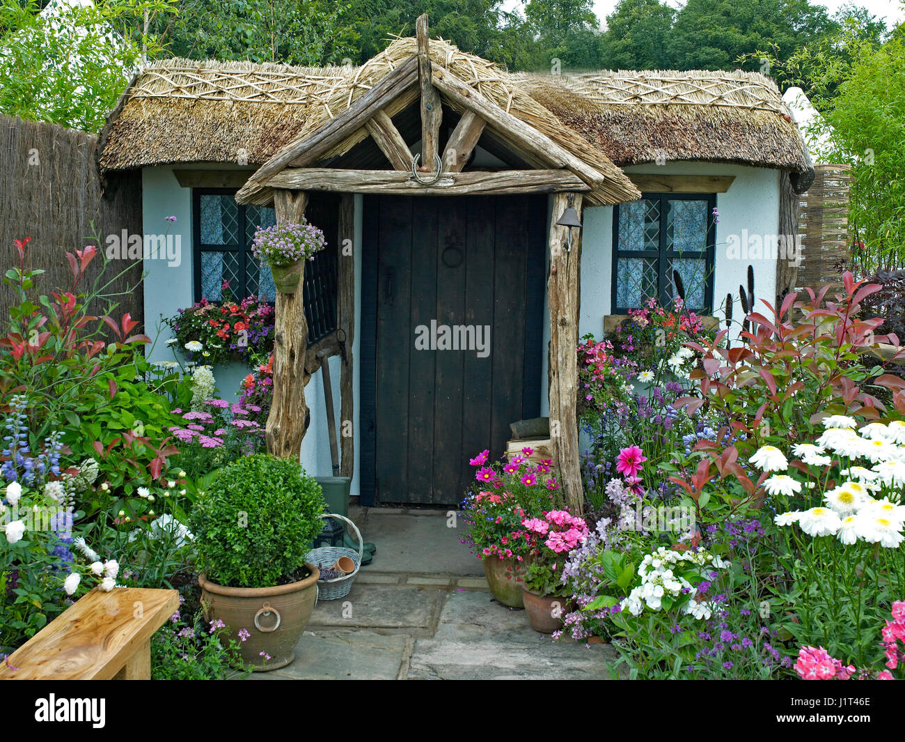 A traditional thatched cottage and garden to creat a calming and relaxing space - Stock Image