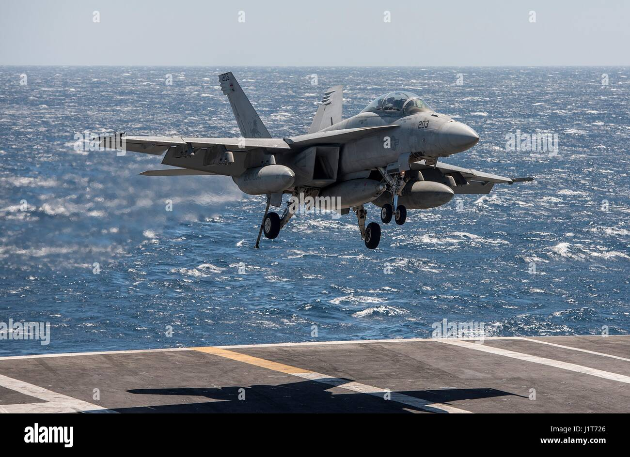 A U.S. Navy F/A-18F Super Hornet fighter aircraft approaches to land on the flight deck of the Nimitz-class aircraft - Stock Image