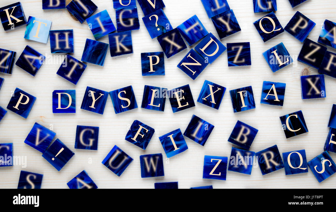 Mosaic pieces with letters in front of wooden background - Concept - Dyslexia - Stock Image