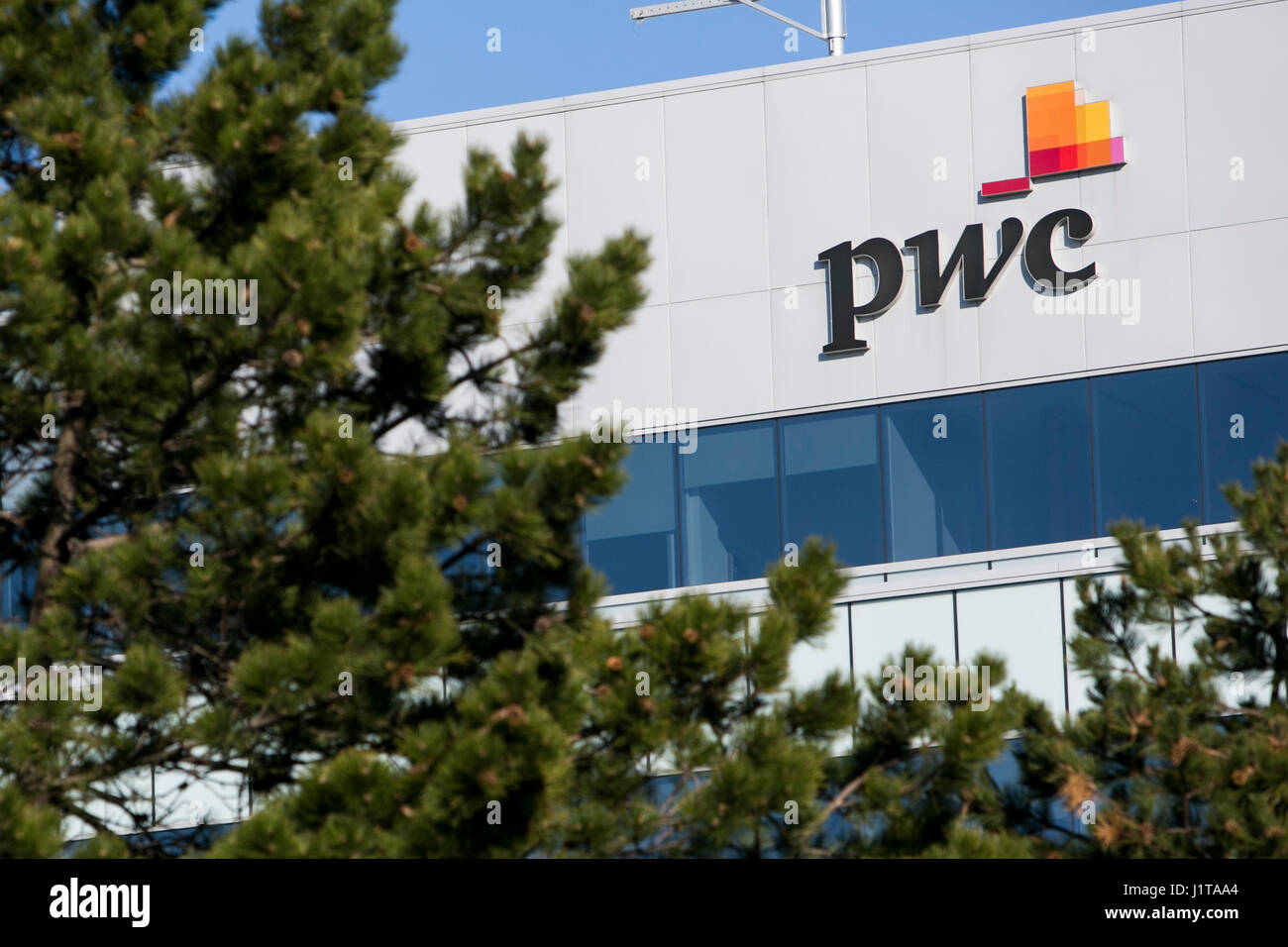 A logo sign outside of a facility occupied by PricewaterhouseCoopers (PWC) in Oakville, Ontario, Canada on April - Stock Image