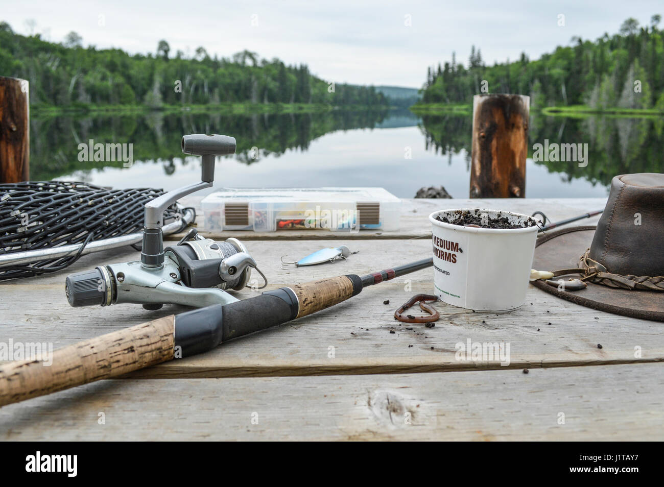 Fishing rod, box of worms, leather hat, some tackles and the fishing net on the pier. - Stock Image