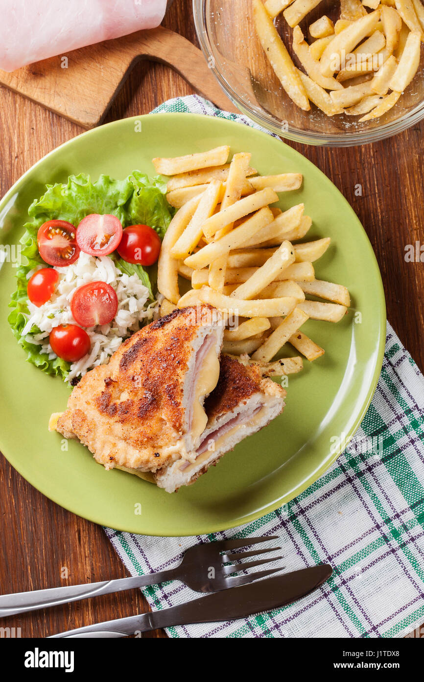 Cutlet Cordon Bleu with pork loin served with French fries and salad on a plate - Stock Image
