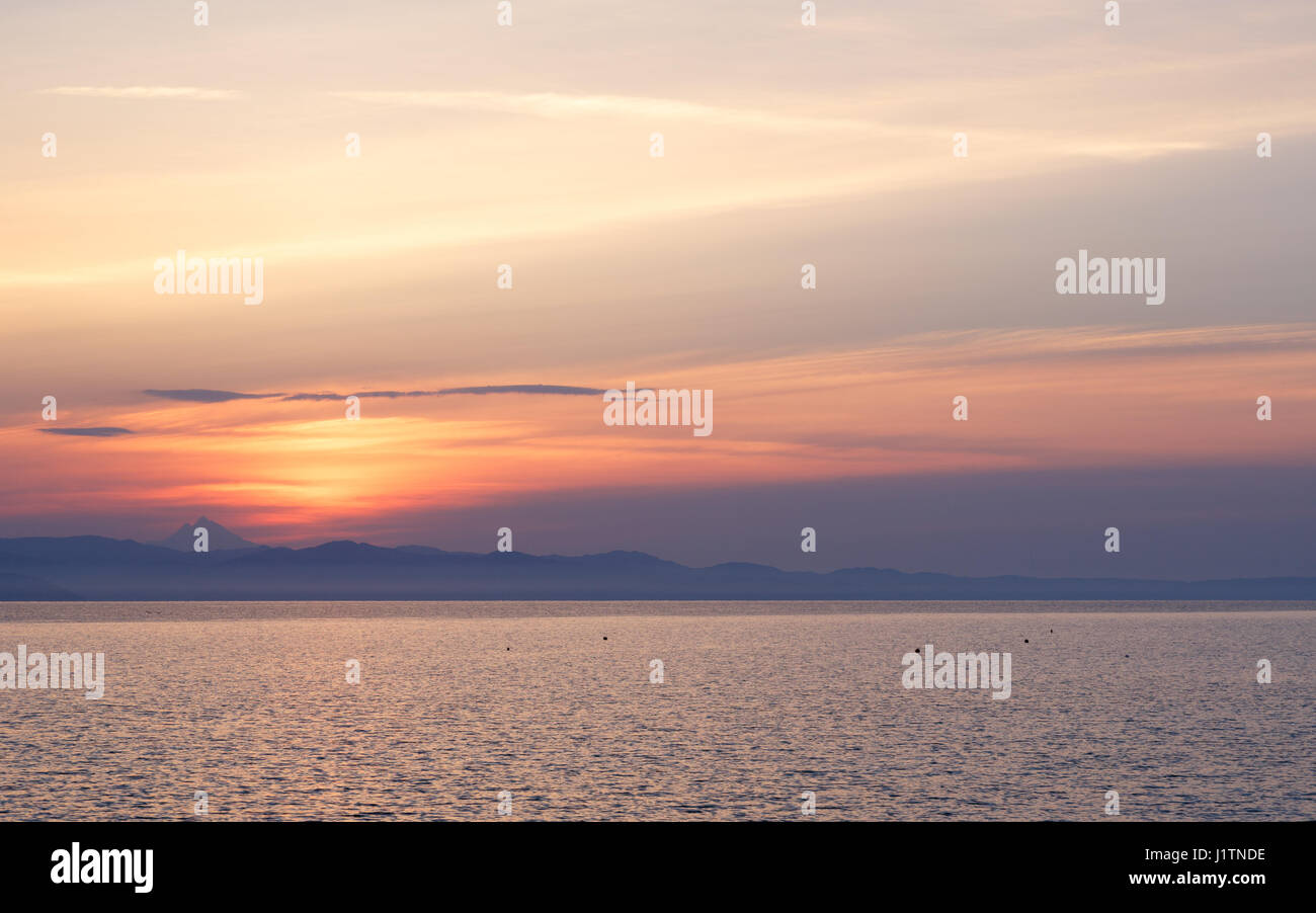 Early morning at dawn of the day with a calm blue sea overlooking the sky and mountains of the other shore, Kassandra, - Stock Image